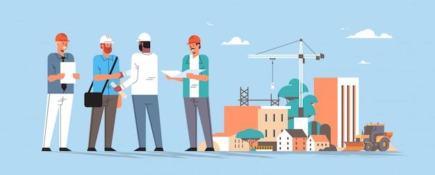 Equipo de constructores estrecharme la mano durante la reunión mezclar carrera ingenieros ingenieros trabajadores en casco discutiendo nuevo proyecto en concepto de acuerdo de apretón de manos plan construcción fondo horizontal de longitud completa