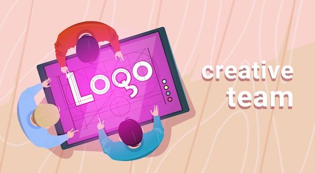 El equipo de diseñadores creativos que trabajan se sientan en el escritorio juntos crean un logotipo web en una tableta digital en la oficina moderna vista en ángulo superior