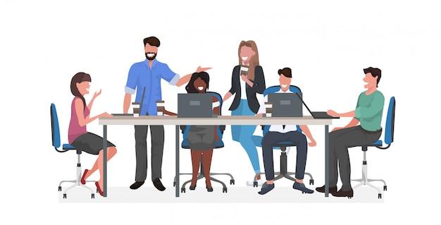 Equipo de empresarios de raza mixta sentado en la mesa redonda discutiendo y bebiendo café durante la reunión de la conferencia