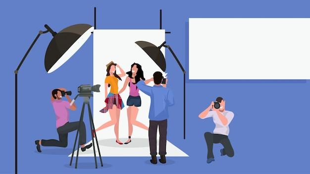 Equipo de fotógrafos profesionales hombres disparando hermosas mujeres modelos de moda posando juntos moderno estudio fotográfico interior horizontal de cuerpo entero