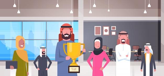Equipo de gente de negocios árabe sosteniendo la copa de oro sobre ilustración de oficina moderna grupo de empresarios ganadores teniendo éxito
