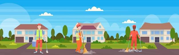 Equipo de limpieza de la calle en uniforme trabajando juntos raza mixta trabajadores masculinos barrido concepto de servicio de limpieza de basura cabaña moderna casa campo fondo plano horizontal de longitud completa