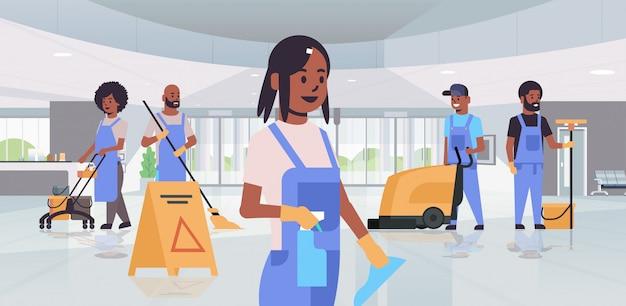 Equipo de limpieza en uniforme trabajando juntos concepto de servicio de limpieza conserjes utilizando equipo profesional vestíbulo del hotel moderno interior horizontal de longitud completa