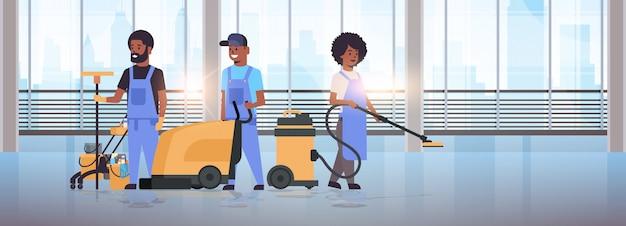 Equipo de limpieza en uniforme trabajando juntos servicio de limpieza concepto conserjes utilizando equipo profesional salón moderno interior ventanas panorámicas de longitud completa horizontal