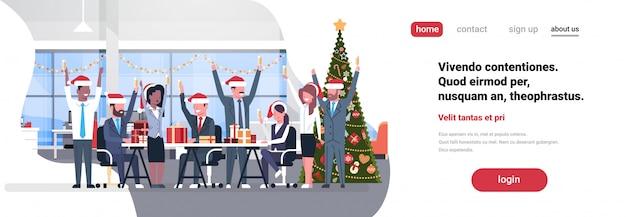 Equipo de negocios levantó las manos en la oficina moderna decorado abeto feliz año nuevo feliz celebración de navidad