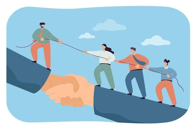 Equipo de negocios trepando apretón de manos gigante con el apoyo del líder