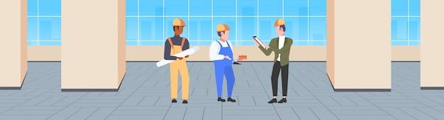 Equipo de trabajadores de la construcción que discute el nuevo proyecto de construcción durante la reunión de constructores de raza mixta en el casco técnicos industriales concepto de trabajo en equipo oficina moderna interior banner horizontal integral