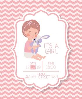 Es una tarjeta de baby shower de niña con niño y conejo relleno.