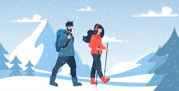 Escaladores de pareja de montaña caminando a través de nevadas