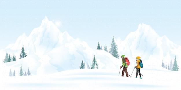 Escaladores de pareja de montaña con mochilas caminando a través de fuertes nevadas en temporada de invierno.