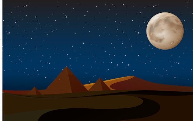 Escena del desierto con pirámides en la noche