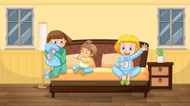 Escena de dormitorio con tres niños en pijama.