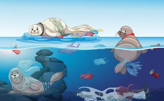 Escena con focas y bolsas de plástico en el océano.