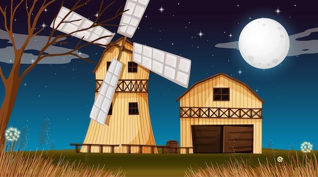 Escena de la granja con granero y molino de viento en la noche.