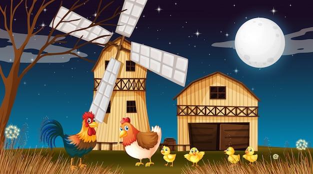 Escena de la granja con granero y molino de viento y pollo por la noche.