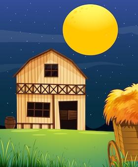 Escena de la granja con granero y paja en la noche.