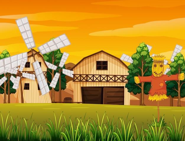 Escena de la granja en la naturaleza con granero y molino de viento y espantapájaros