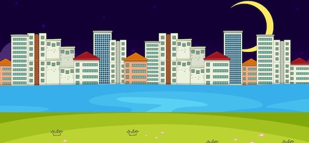 Escena horizontal con río y paisaje urbano por la noche.