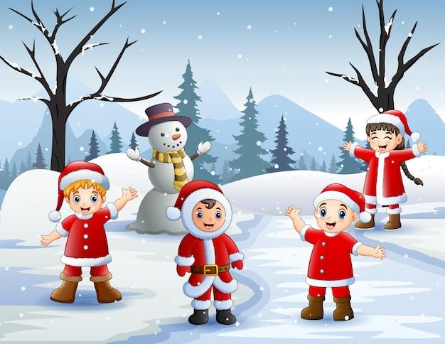 Escena de invierno con niños disfrazados de santa y muñeco de nieve.