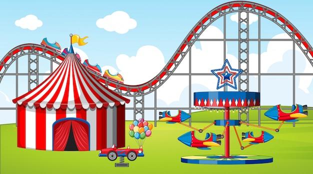 Escena con muchas atracciones y carpa de circo en el campo.