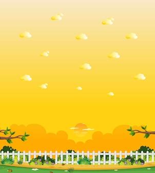 Escena de la naturaleza vertical o paisaje de campo con parte de la valla en la vista de la granja y vista del cielo amarillo del atardecer