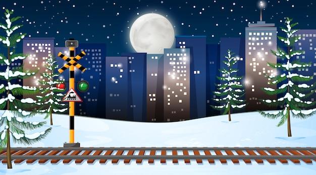 Escena de nieve con vías de tren en la noche