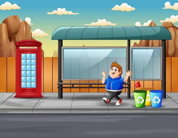 Escena con niño gordo tira basura a la basura.