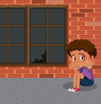 Escena con niño llorando sentado solo en el edificio