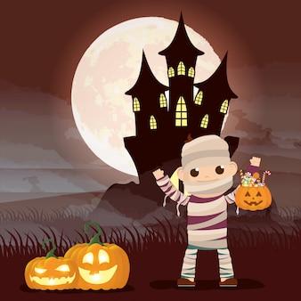 Escena de la noche oscura de halloween con calabazas y momia disfrazada de niño