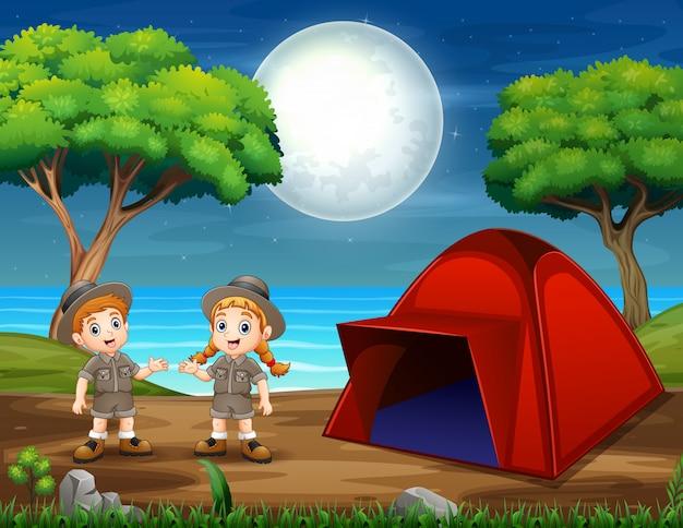 Escena nocturna de camping con dos exploradores