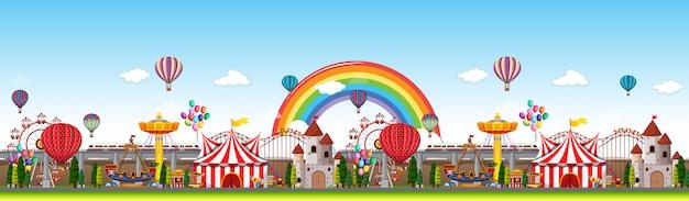 Escena panorámica del parque de atracciones durante el día con arco iris en el cielo