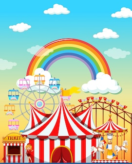 Escena del parque de atracciones durante el día con arco iris en el cielo