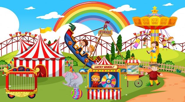 Escena del parque de atracciones durante el día con arco iris en el cielo.