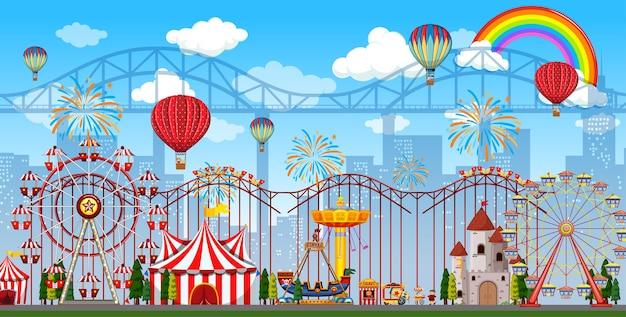 Escena del parque de atracciones durante el día con arco iris y globos en el cielo.