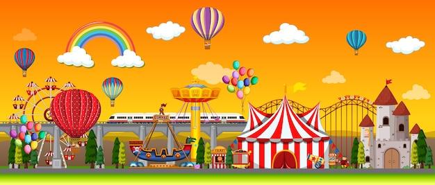 Escena del parque de atracciones durante el día con globos y arco iris en el cielo