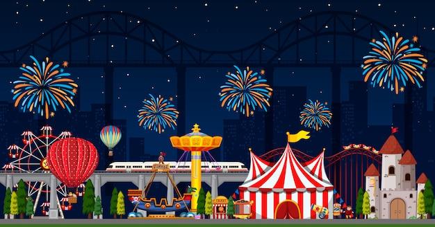 Escena del parque de atracciones en la noche con fuegos artificiales en el cielo