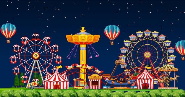 Escena del parque de atracciones en la noche con globos en el cielo