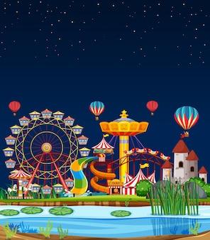 Escena del parque de atracciones en la noche con globos en el cielo.