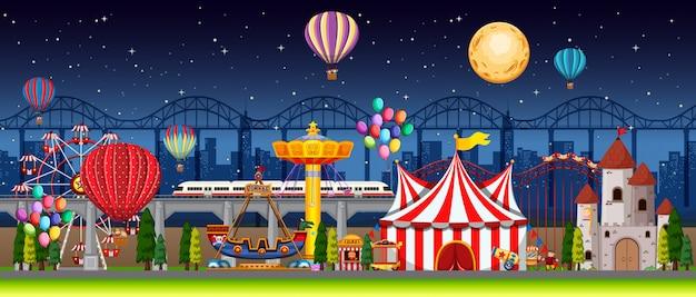 Escena del parque de atracciones en la noche con globos y luna en el cielo.