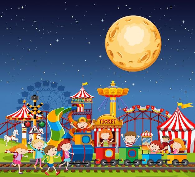 Escena del parque de atracciones en la noche con gran luna en el cielo