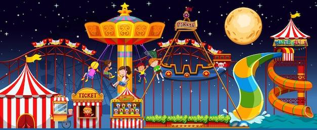 Escena del parque de atracciones en la noche con luna en el cielo.