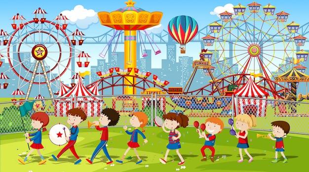 Escena del parque temático con muchos paseos con niños en la banda.