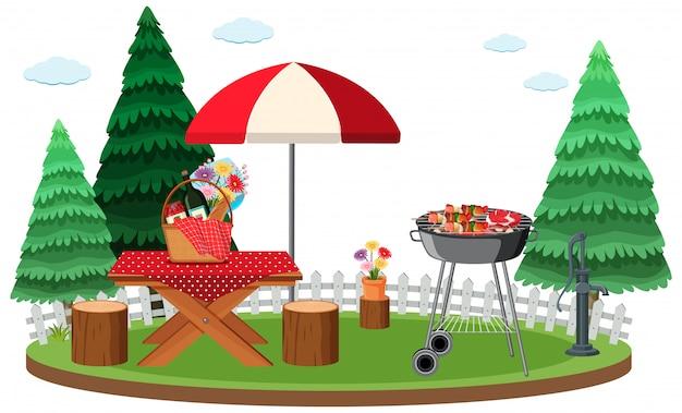 Escena de picnic con comida en la mesa y parrilla de barbacoa en el jardín.