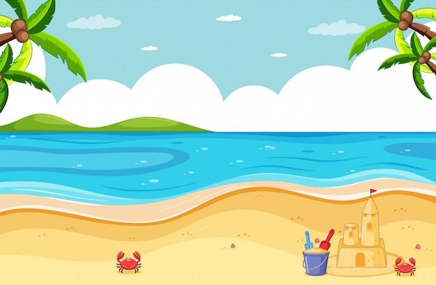 Escena de playa con castillo de arena y cangrejo pequeño