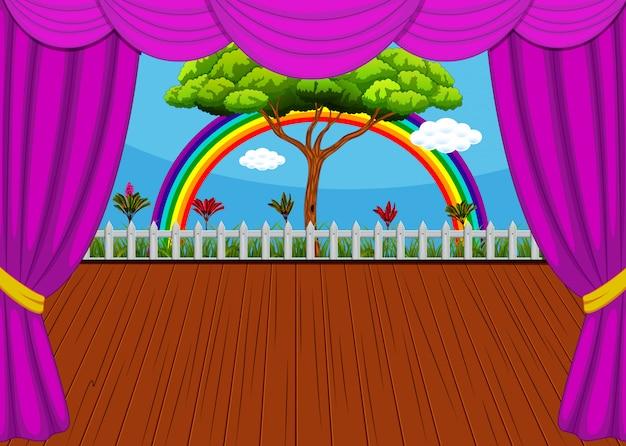 El escenario con arco iris y fondo de árbol.