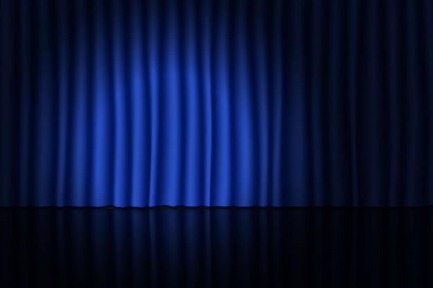 Escenario con cortina azul y proyector.