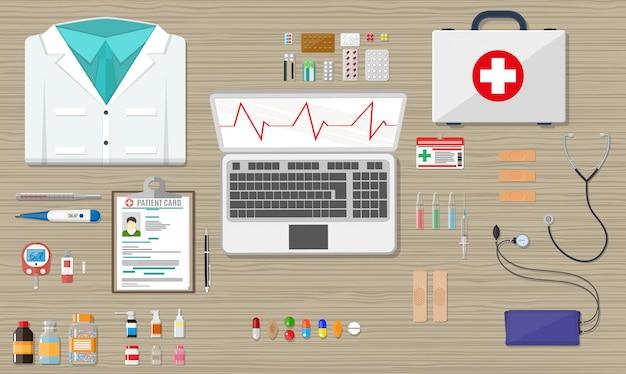 Escritorio con laptop, dispositivos médicos y sanitarios.
