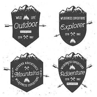 Escudos con montañas conjunto de cuatro insignias vintage vector