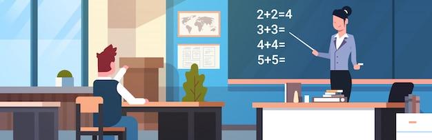 Escuela lección matemática maestra con alumno chico en aula