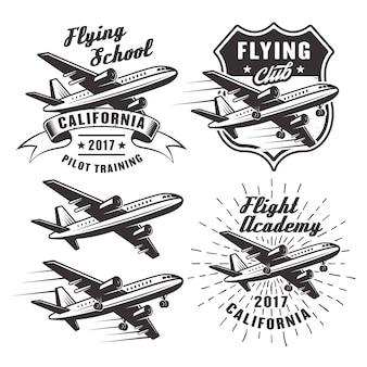 Escuela de vuelo conjunto de emblemas, etiquetas y elementos con avión de pasajeros en monocromo sobre fondo blanco.